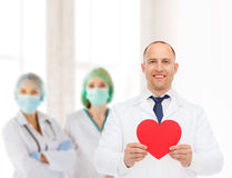Smiling male doctor with red heart Stock Photos