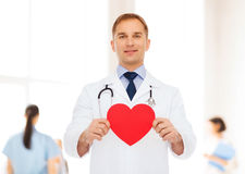 Smiling male doctor with red heart and stethoscope Stock Photos
