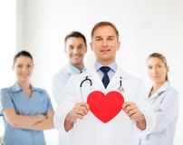 Smiling male doctor with red heart and stethoscope Royalty Free Stock Images