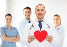 Smiling male doctor with red heart and stethoscope Royalty Free Stock Photo
