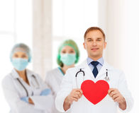 Smiling male doctor with red heart and stethoscope Royalty Free Stock Image