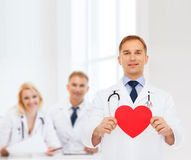 Smiling male doctor with red heart and stethoscope Royalty Free Stock Photos