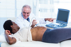 Smiling male doctor showing results on monitor Royalty Free Stock Photo