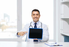 Smiling male doctor showing tablet pc blank screen Royalty Free Stock Image