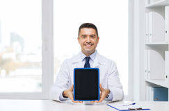 Smiling male doctor showing tablet pc blank screen Royalty Free Stock Photos