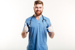 Smiling male doctor showing thumbs up gesture with two hands Stock Photography
