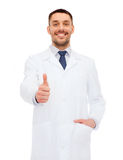 Smiling male doctor showing thumbs up Stock Photos