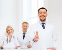 Smiling male doctor showing thumbs up Stock Image