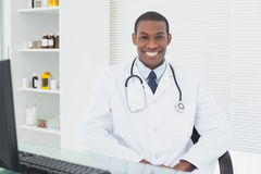 Smiling male doctor sitting with computer at medical office Stock Images