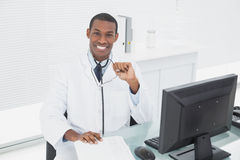 Smiling male doctor sitting with computer at medical office Royalty Free Stock Photos