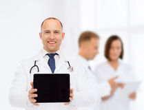Smiling male doctor with stethoscope and tablet pc Stock Photos