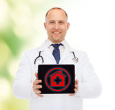Smiling male doctor with stethoscope and tablet pc Stock Image