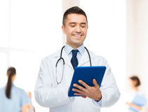 Smiling male doctor with tablet pc at hospital Stock Photography