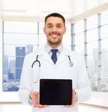 Smiling male doctor with tablet pc. Medicine, advertisement and people concept - smiling male doctor showing tablet pc computer blank screen over white room Royalty Free Stock Photos