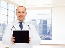 Smiling male doctor with tablet pc. Medicine, advertisement and people concept - smiling male doctor showing tablet pc computer blank screen over white room Stock Photo