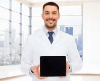 Smiling male doctor with tablet pc. Medicine, advertisement and people concept - smiling male doctor showing tablet pc computer blank screen over white room Royalty Free Stock Images