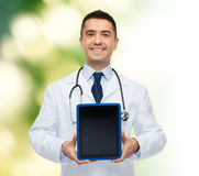 Smiling male doctor with tablet pc Royalty Free Stock Images