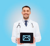 Smiling male doctor with tablet pc Stock Images