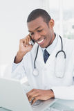 Smiling male doctor using cellphone and laptop Stock Photos