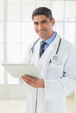 Smiling male doctor using digital tablet Stock Photos