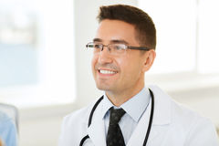 Smiling male doctor in white coat and eyeglasses Stock Photo