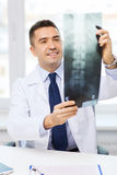 Smiling male doctor in white coat looking at x-ray Stock Photos