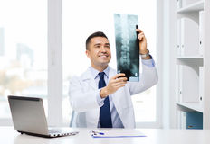 Smiling male doctor in white coat looking at x-ray Stock Photography