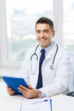 Smiling male doctor in white coat with tablet pc Stock Photos