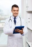 Smiling male doctor in white coat with tablet pc Royalty Free Stock Images