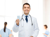 Smiling male doctor in white coat with tablets Stock Photos