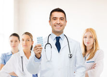 Smiling male doctor in white coat with tablets Royalty Free Stock Photo