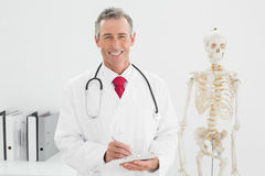 Smiling male doctor writing a report at office Royalty Free Stock Image