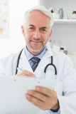 Smiling male doctor writing reports in medical office Royalty Free Stock Photos