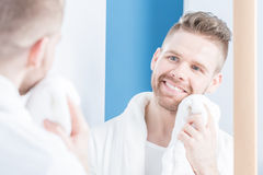 Smiling male drying face Stock Image