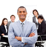 Smiling male executive with folded arms. Sitting in front of his team in a meeting Stock Photo