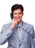 Smiling male executive tangle up in phone wires Royalty Free Stock Image