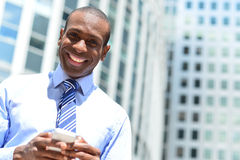 Smiling male executive using his mobile phone. African handsome businessman at outdoors with smart phone Royalty Free Stock Images
