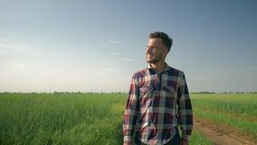 Smiling male farmer enjoy the fresh air and the beauty of nature, young man goes to camera on background of green field. Smiling male farmer enjoy the fresh air stock footage