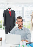 Smiling male fashion designer using laptop in the studio Stock Photos
