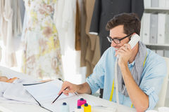 Smiling male fashion designer using phone in the studio Royalty Free Stock Image