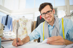 Smiling male fashion designer working on his designs. Portrait of a smiling young male fashion designer working on his designs in the studio Royalty Free Stock Photography