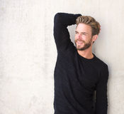 Smiling male fashion model posing in black sweater. Portrait of a smiling male fashion model posing in black sweater Royalty Free Stock Photo