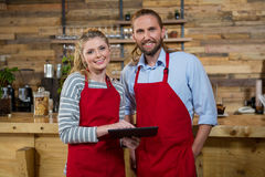 Smiling male and female baristas using digital tablet in coffee shop. Portrait of smiling male and female baristas using digital tablet in coffee shop Royalty Free Stock Photos
