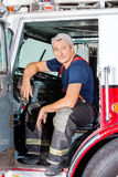 Smiling Male Firefighter Sitting In Truck Royalty Free Stock Image