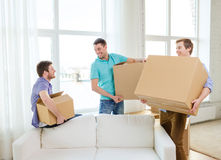 Smiling male friends carrying boxes at new place. Moving, real estate and friendship concept - smiling male friends carrying boxes at new place stock photos