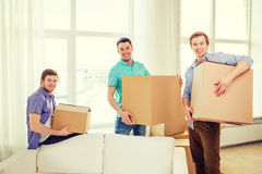 Smiling male friends carrying boxes at new place Royalty Free Stock Photo