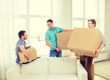 Smiling male friends carrying boxes at new place Royalty Free Stock Photos