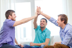 Smiling male friends giving high five at home Stock Photo