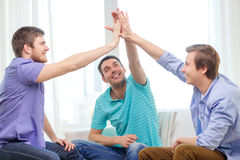 Smiling male friends giving high five at home Stock Image