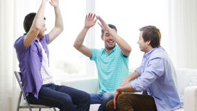 Smiling male friends giving high five at home Stock Photography